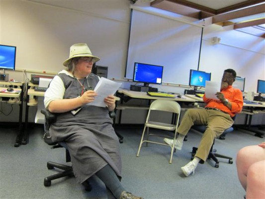 Two volunteers sit in the STAR Center reading over informational documents.