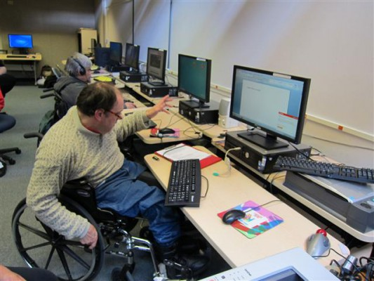 Tom pulls his wheel chair up to a computer inside the STAR Center
