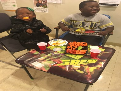 Two young children sit at the kids table at the STAR Open House Event right outside of the STAR center. They are enjoying vegetable snacks.