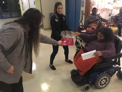 Two volunteers lean out to Chastity in a wheelchair so that she can draw her raffle ticket from the basket and claim her prize.